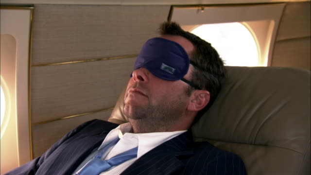 close-up businessman wearing sleep mask and reclining in private airplane - zurücklehnen stock-videos und b-roll-filmmaterial