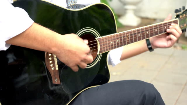 closeup businessmen are playing acoustic guitar after returning from work. - musical symbol stock videos & royalty-free footage