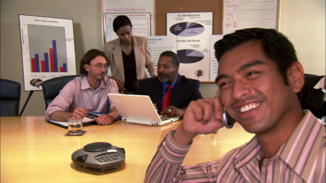 close-up businesspeople using laptop and businessman talking on cell phone in conference room - goatee stock videos & royalty-free footage