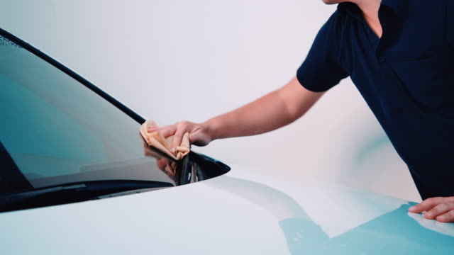 4k close-up car cleaning staff he is using yellow microfiber cloth. wipe the white car clean in the car wash shop - car wash stock videos & royalty-free footage