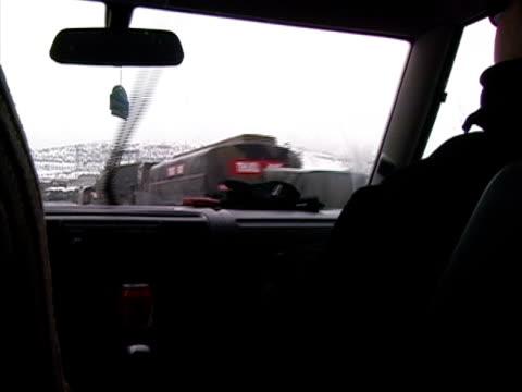 stockvideo's en b-roll-footage met closeup car driving in rain past military convoy along roadside/ turkey - passagiersstoel