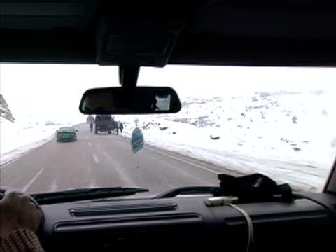 stockvideo's en b-roll-footage met closeup car driving in rain past military vehicles along roadside/ turkey - passagiersstoel