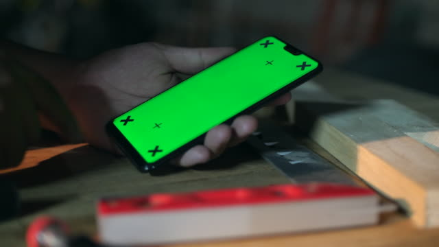 close-up carpenter using mobile phone with green screen in workshop, chroma key - strike industrial action stock videos & royalty-free footage