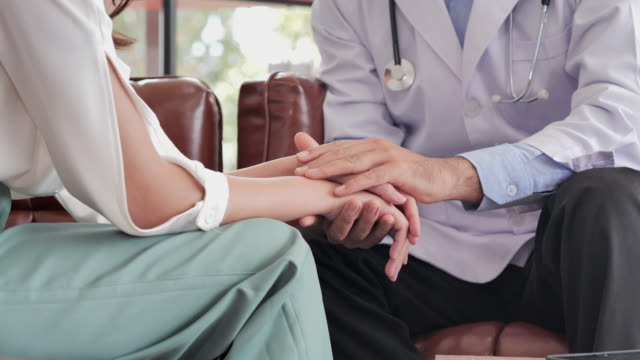 close-up caucasian male doctor in consultation to her asian young women patient while holding hand to her patient help express empathy encourage tell diagnosis at medical visit at hospital.helping hands - emotional support stock videos & royalty-free footage