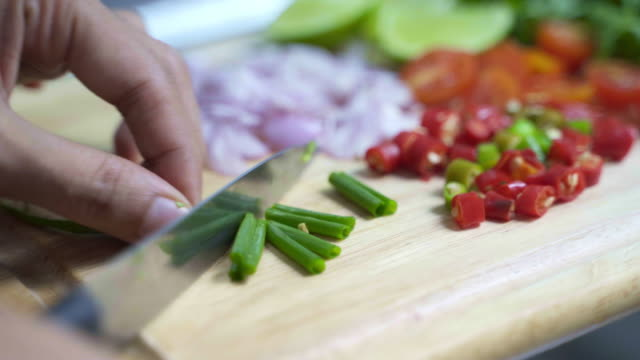 closeup chef cutting fresh chilli, onions, tomatoes, limes and parsley to making fried fish spicy salad thai food with knife on cutting board. - chopping board stock videos & royalty-free footage