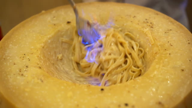 closeup chef hand cooking pasta on cheese with fire - top capo di vestiario video stock e b–roll