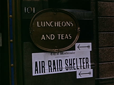 vidéos et rushes de closeup city of westminster sign handing outside tea shop reading 'air raid shelter' during war preparations / westminster london england - écriture européenne