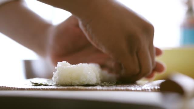 vídeos de stock, filmes e b-roll de mãos do close-up cook fazendo sushi roll - comida japonesa