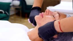 close-up, cosmetologist, in black medical gloves, removes remains of cosmetic face product, from female face with special wet wipes. skincare procedure in cosmetology clinic or beauty salon