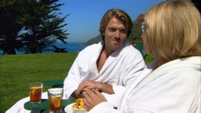 close-up couple eating fruit and relaxing in deck chairs at spa/ monterey county, california, usa - ragged point stock videos and b-roll footage