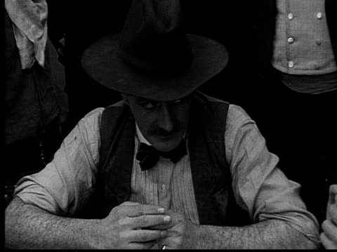 stockvideo's en b-roll-footage met 1915 b/w close-up cowboy playing poker in gambling saloon  - 1915