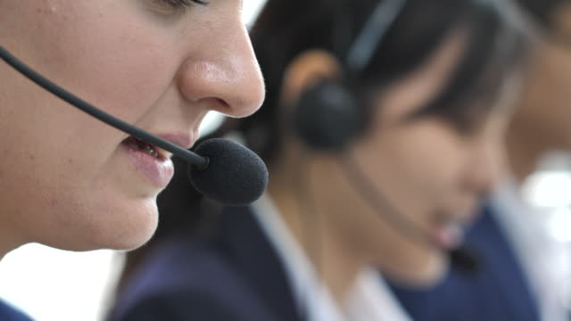 close-up customer support workers team are working in call center in office - females stock videos & royalty-free footage