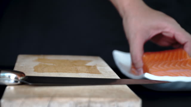 4k close-up cutting raw fresh salmon on wooden chopping board - plate stock videos & royalty-free footage