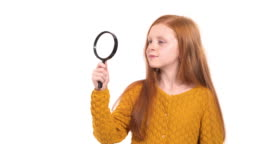 Close-up demonstration video of a little charming model girl with beautiful foxy hair looking through a magnifying glass. Isolated, on white background