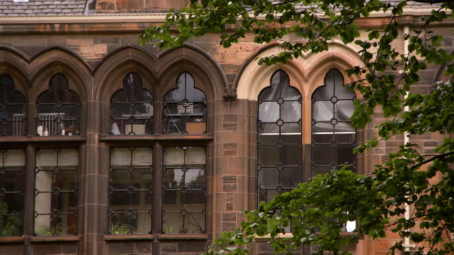 close-up detail and tilt down of gothic glasgow university building exterior, with windows, arches, slate roof tiles, and red sandstone bricks - moving down stock videos & royalty-free footage