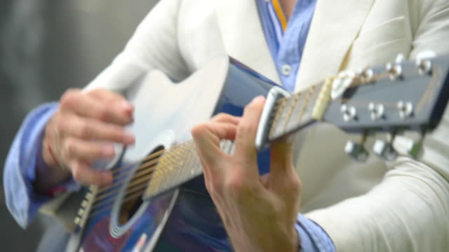 vidéos et rushes de close-up detail of a man playing guitar hands. - slow motion - doigt humain