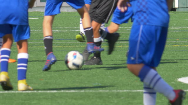 closeup detail of a soccer football ball getting kicked on a turf grass field. - slow motion - contestant stock videos & royalty-free footage