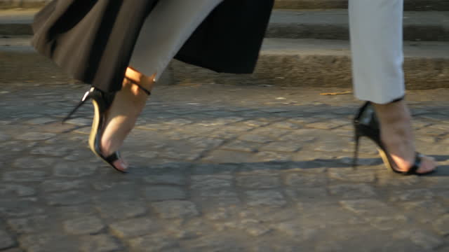 close-up details of a woman feet walking in black high heel shoes and overcoat on a cobblestone street. - slow motion - オーバーコート点の映像素材/bロール