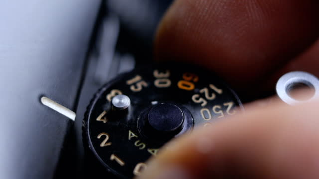 close-up details of an old vintage slr film camera and fingers adjusting the exposure speed dial - shutter stock videos & royalty-free footage