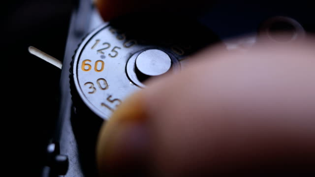 close-up details of an old vintage slr film camera and fingers adjusting the exposure speed dial with click sound included - switch stock videos & royalty-free footage