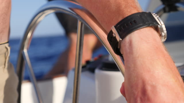 close-up details of hands on a steering wheel at the helm sailing on a sailboat boat in the pacific ocean. - slow motion - sailing stock videos & royalty-free footage