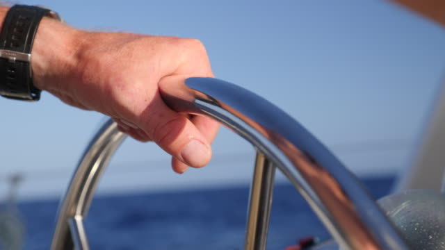 vidéos et rushes de close-up details of hands on a steering wheel at the helm sailing on a sailboat boat in the pacific ocean. - slow motion - voilier