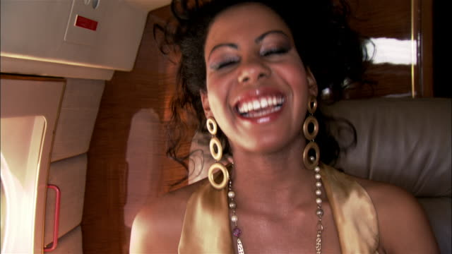 close-up diva smiling and wearing gold earrings on private airplane - halskette stock-videos und b-roll-filmmaterial