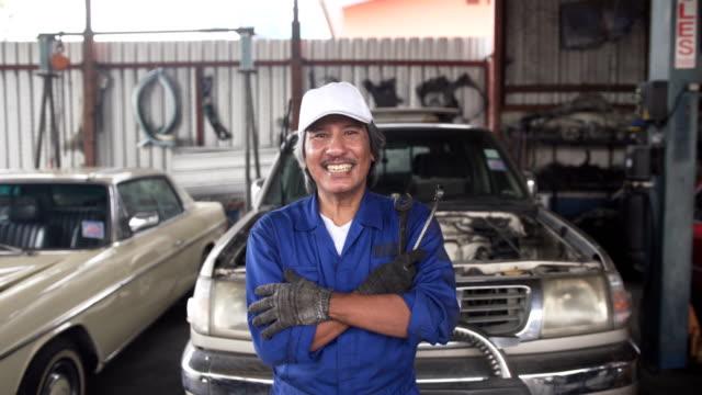 närbild dolly: asiatiska senior bilmekaniker leende och är stolta över jobbet - 55 59 år bildbanksvideor och videomaterial från bakom kulisserna