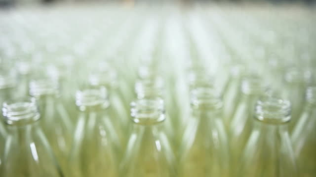 close-up dolly shot: glass drinking transparent bottles - beer cap stock videos & royalty-free footage