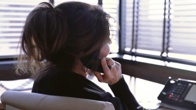 close-up dolly shot of businesswoman talking on landline phone at desk - 加入電話点の映像素材/bロール