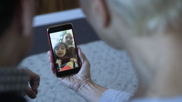Close-up dolly shot of couple video calling on mobile phone at home