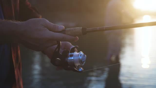 close-up dolly shot of man using fishing rod at lake - remote location stock videos & royalty-free footage
