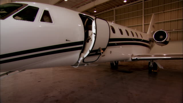 close-up door of private jet opening in hangar at opa locka airport/ miami, florida, usa - airplane hangar stock videos and b-roll footage
