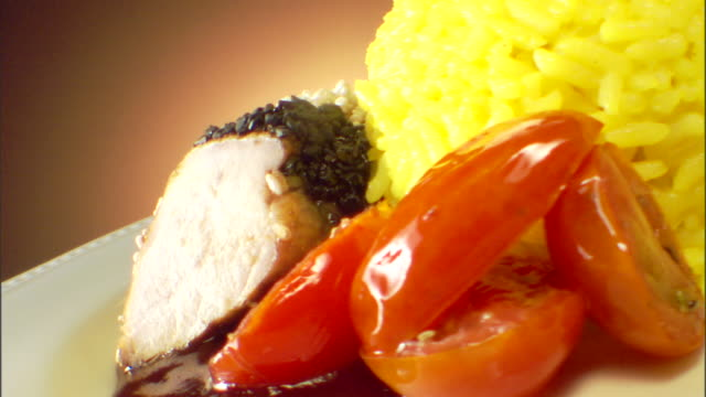 Close-up dutch angle view of a rotating plate of sliced pork and yellow rice.