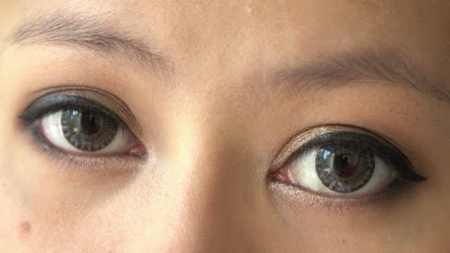 close-up eye woman makeup beauty looking at camera