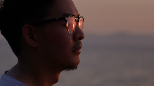 close-up face of asian man in eyeglasses looking at sunset with sunlight reflection - hope stock videos & royalty-free footage