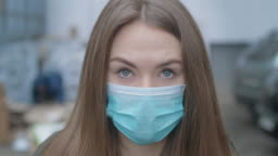 Close-up face of girl in protective mask looking at camera. Young beautiful brunette woman with grey eyes outdoors in city. Pandemic, medicine, Covid-19. Cinema 4k ProRes HQ.