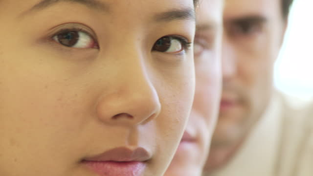 Closeup face portrait of three young business colleagues