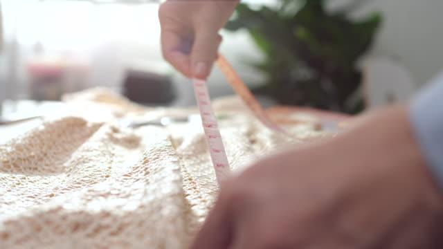 vídeos de stock e filmes b-roll de close-up fashion designer using a measuring on dress - primeiríssimo plano