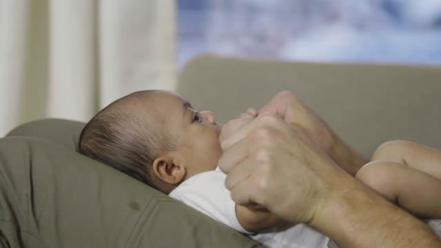 彼の赤ちゃんの女の子の手を繋いでいるクローズ アップの父 - 生後2ヶ月から5ヶ月点の映像素材/bロール
