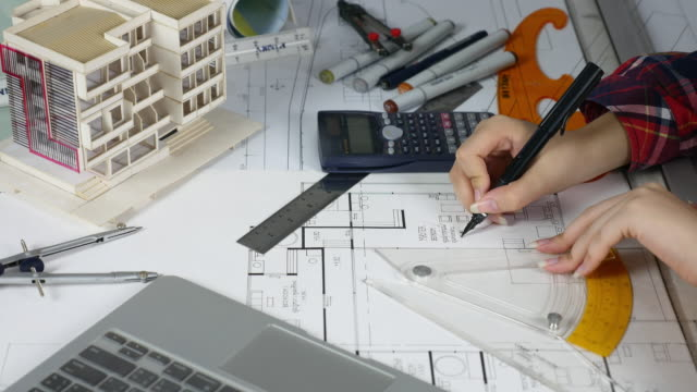 Close-up Female architect Hand working at desk with plans on blueprint with Artificial Model and Laptop