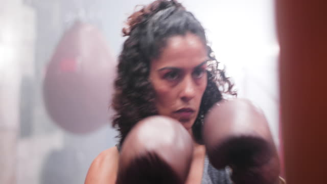 vidéos et rushes de closeup female boxer punching a punch bag - musclé