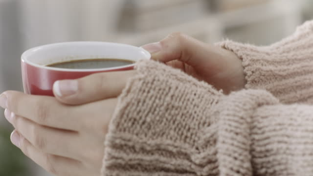 close-up, female hands hold a red coffee cup - jumper stock videos & royalty-free footage