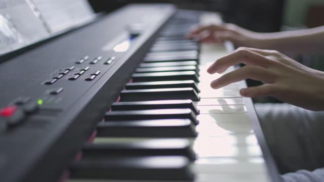 vidéos et rushes de doigts de plan rapproché de fille appuyant sur les touches de piano. les mains de la femme joue le solo de la musique dans la vue latérale - zoom arrière
