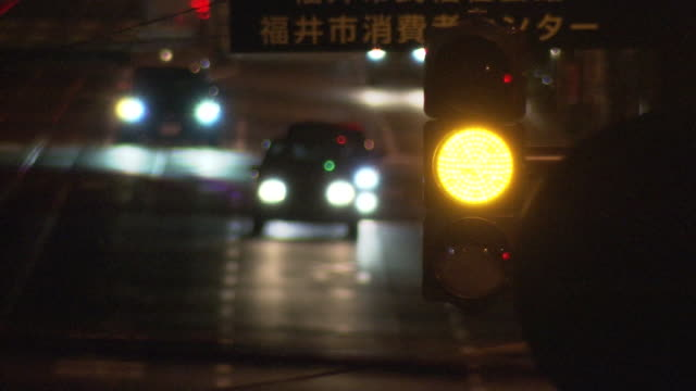 close-up; flashing yellow signal at night, fukui, japan - road signal stock videos & royalty-free footage