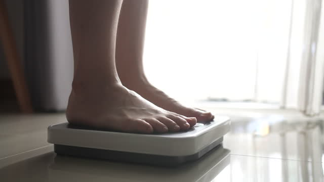 vídeos de stock e filmes b-roll de close-up foot of woman walking on a body weighing scale - alimentação não saudável