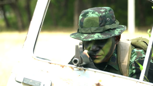 close-up front of  view: Fully Equipped and face-camouflaged Soldiers is ready to fight behind car door