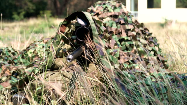 close-up front view: fully equipped and cloth-camouflaged sniper waiting among grass under camouflaged covering - military recruit stock videos & royalty-free footage