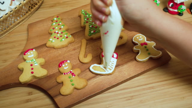 close-up front view: human's hand using red and white icing sugar to preparing, decorating icing, homemade christmas cookies, gingerbread, tree, and star on wooden christmas table. some cookies are on a wooden plate - biscuit stock videos & royalty-free footage
