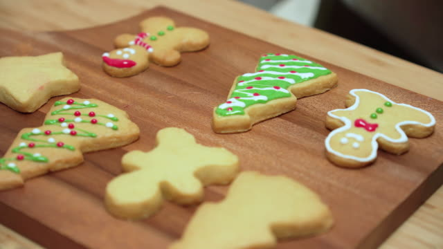 close-up front view: human's hand using red icing sugar to preparing, decorating icing, homemade christmas cookies, gingerbread, tree, and star on wooden christmas table. some cookies are on a wooden plate - buttermilk biscuit stock videos & royalty-free footage